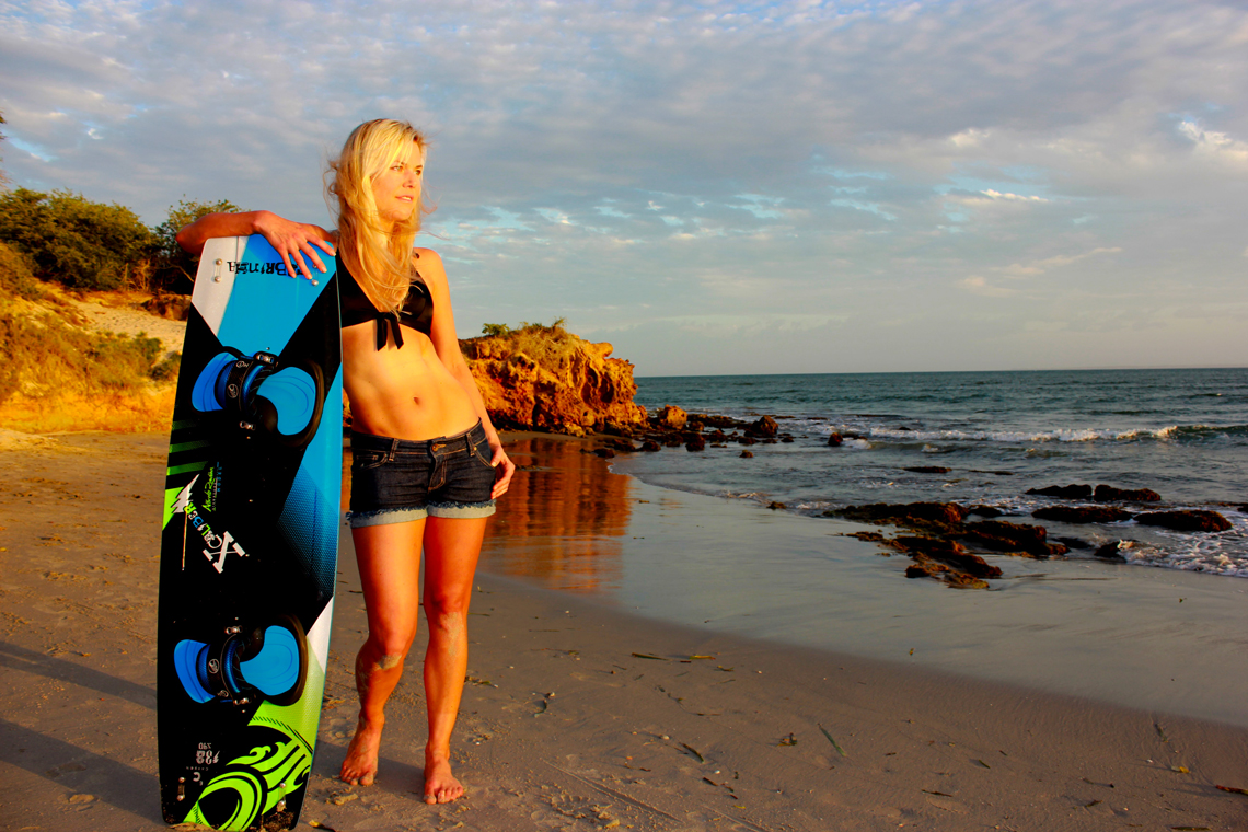 Making the Cabrinha Xcaliber board look good - girl posing with kiteboard