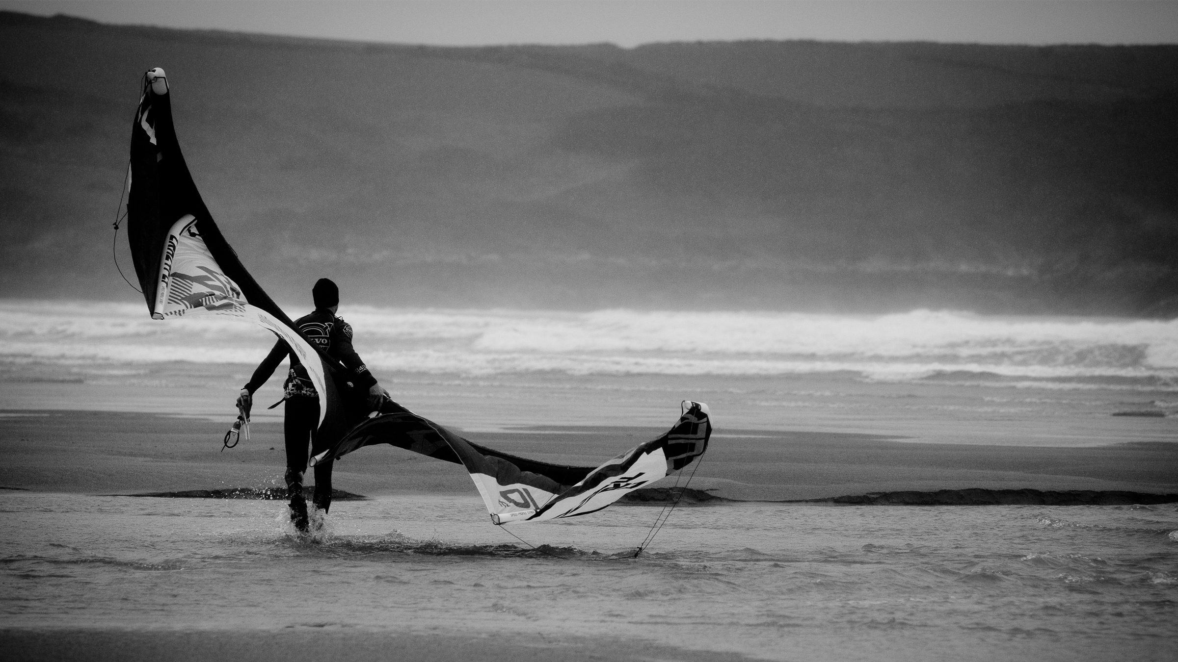 kitesurf wallpaper image - Kitesurfer walking on the beach with his kite. - in resolution: High Definition - HD 16:9 2400 X 1350