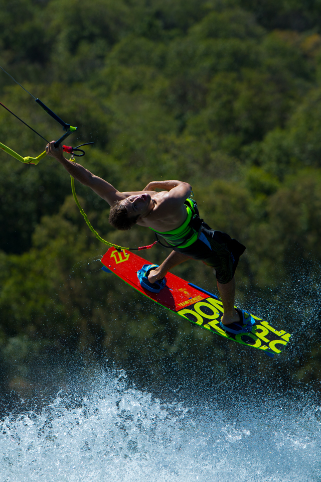 kitesurf wallpaper image - Tom Hebert swinging on one arm and riding the 2015 North Team Series - North kiteboarding - in resolution: iPhone 640 X 960