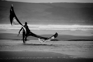 Kitesurfer walking on the beach with his kite.